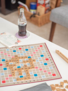 A game of scrabble set up on a table. Two bottles of Coke, and a notepad with scores are on the table next to it.