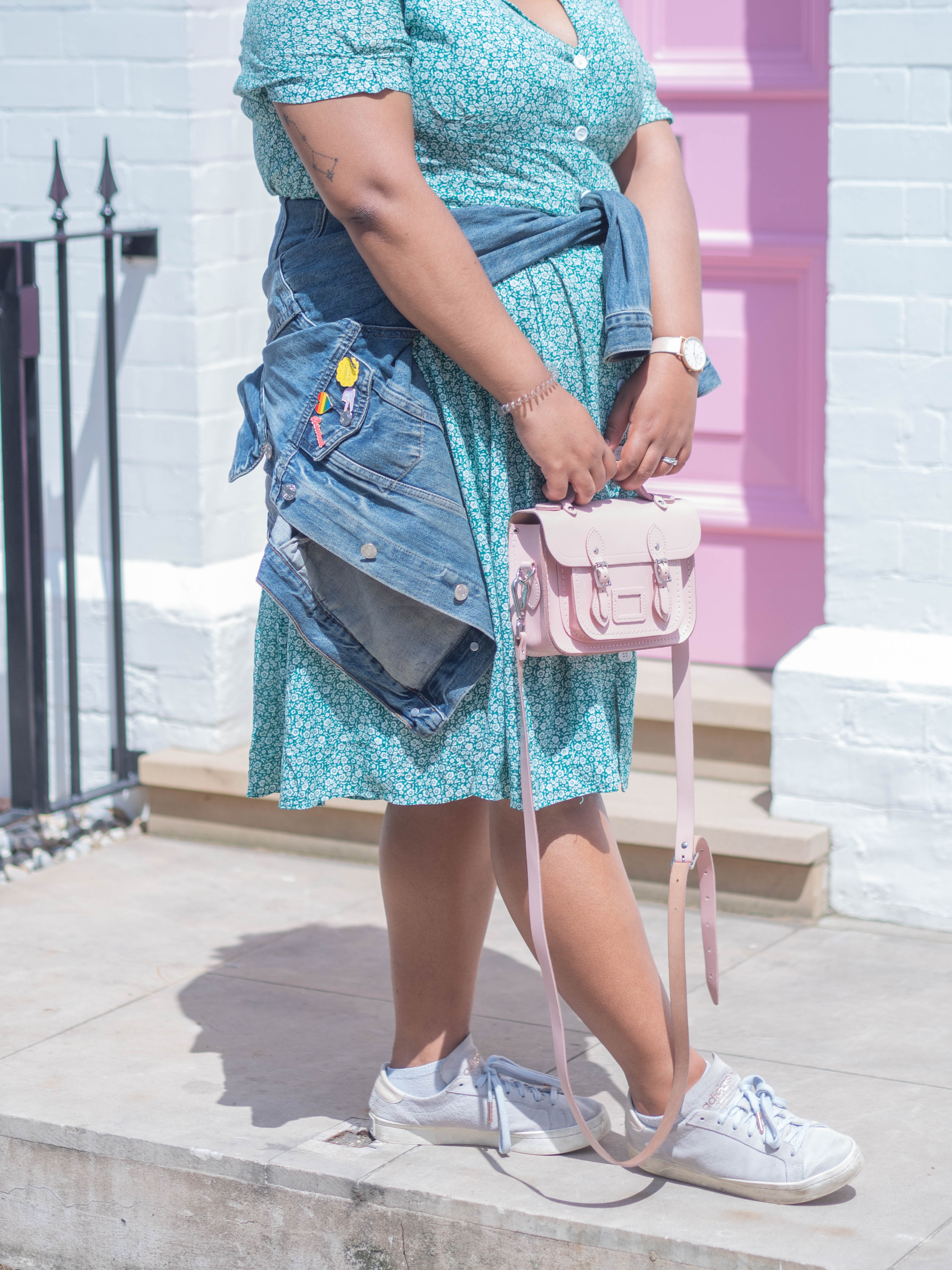 A close up of Ghenet's outfit: a pink satchel bag, a denim jacket tied at the waist, adorned with pin badges.