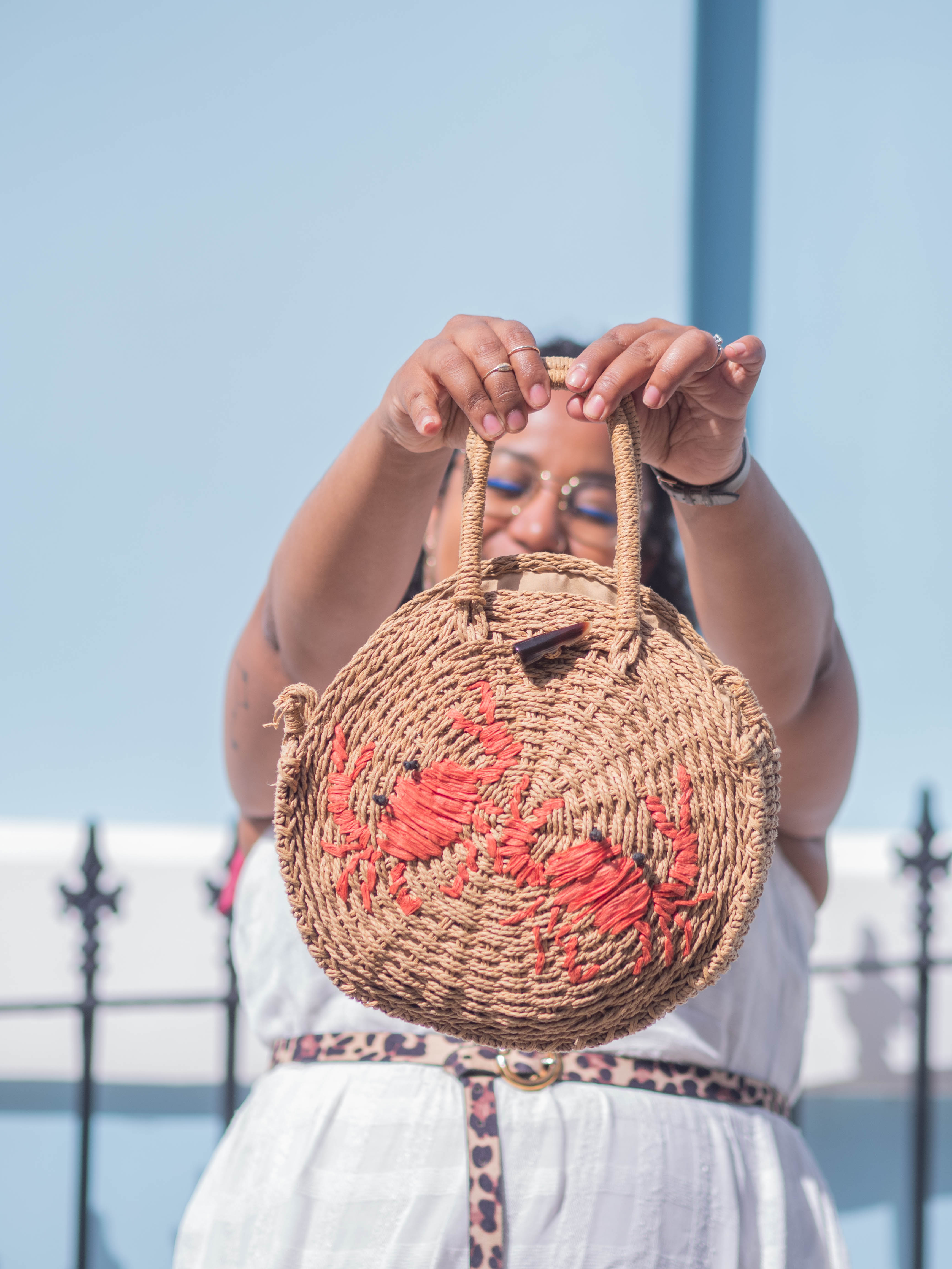 Ghenet stands in the sunshine, holding up a straw bag with red crabs on it.