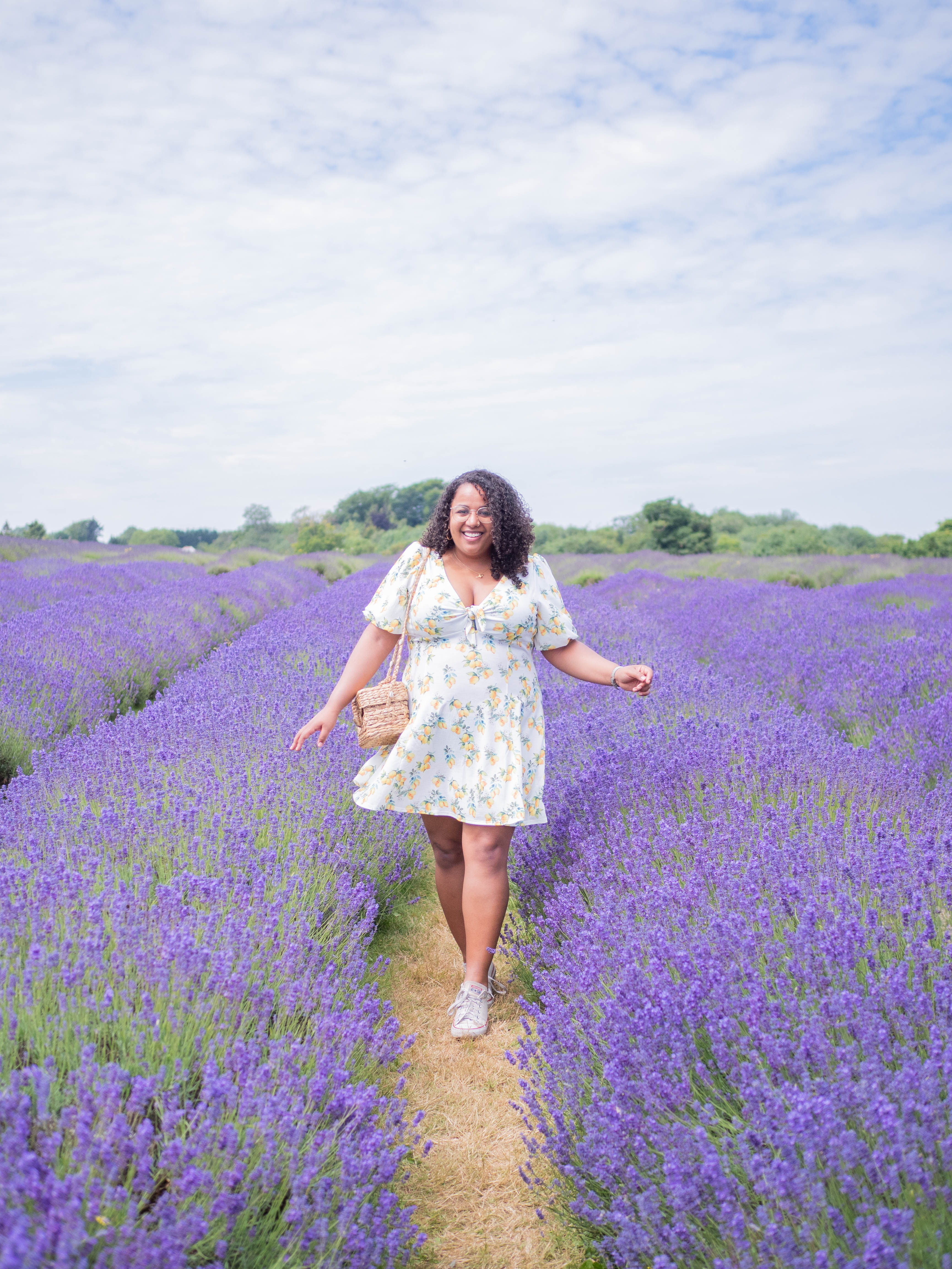 Ghenet stands among the lavender at Mayfield Lavender Farm, in a lemon print dress and a wicker bag.