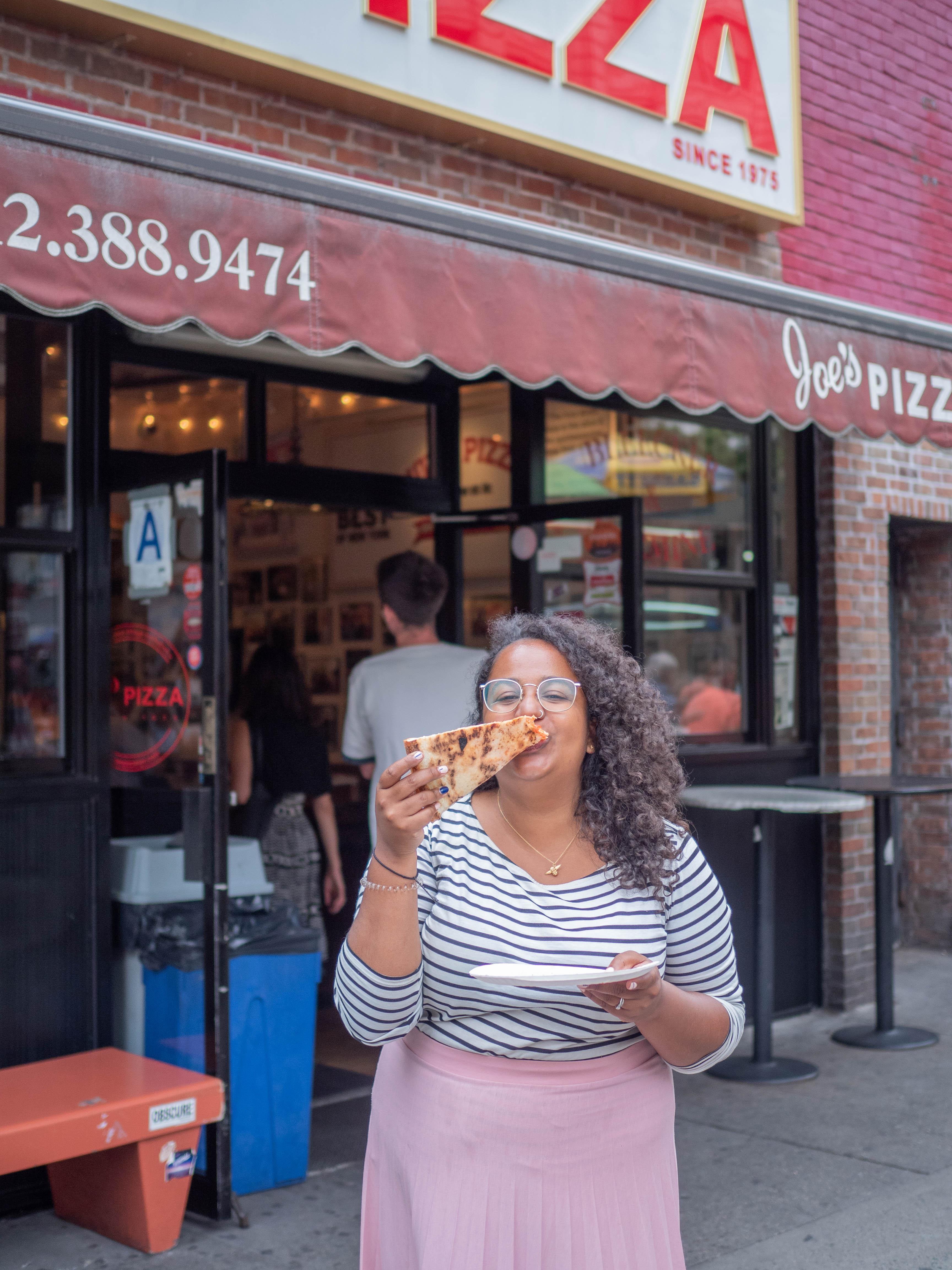 Ghenet stands outside Joe's Pizza enjoying a slice!